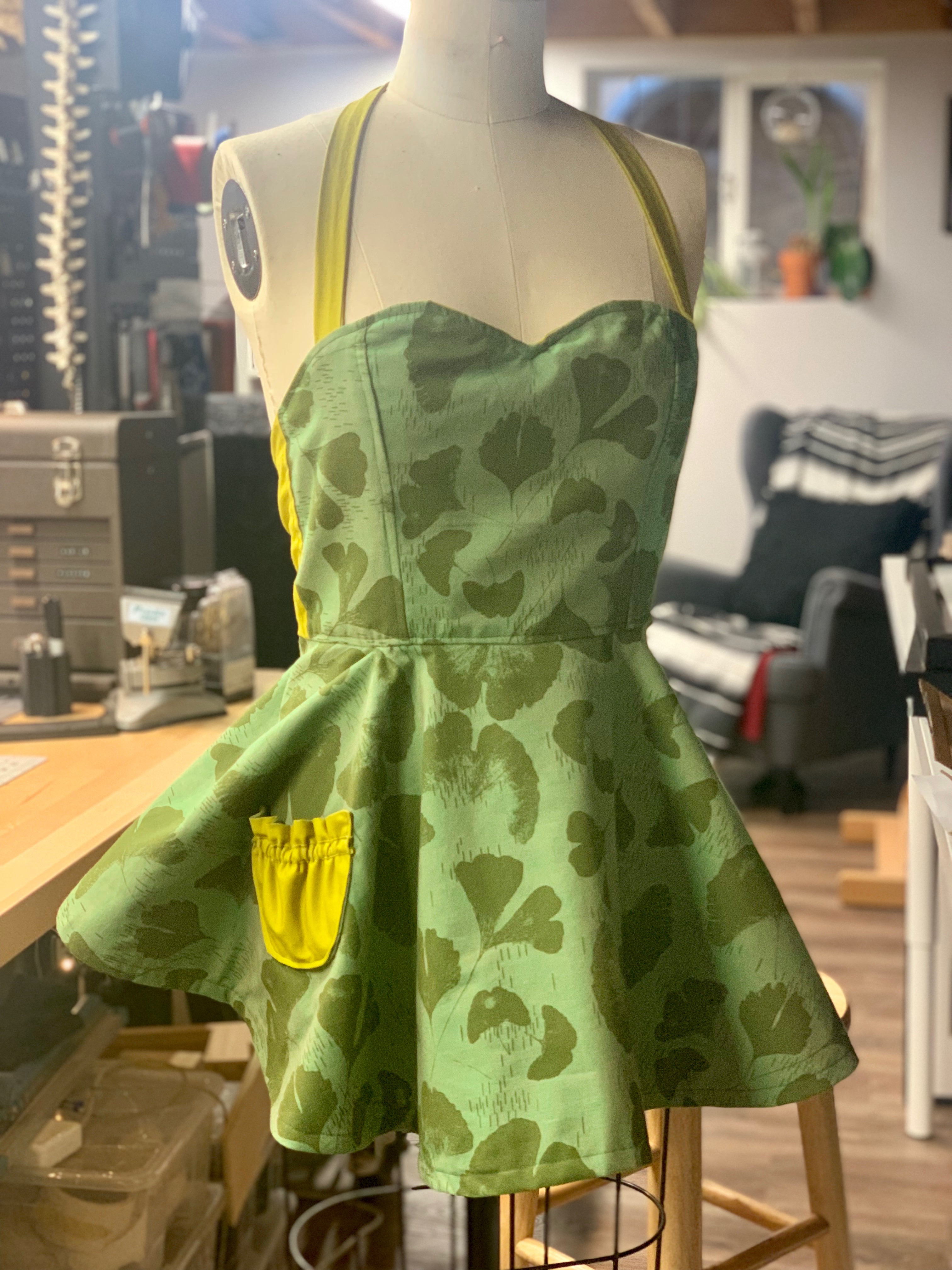 A front view of the apron, featuring a ginkgo leaf motif in shades of green